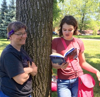 Teacher Lou Hopping listens to a recent 8th grade graduate read aloud from Wishtree by Katherine Applegate.