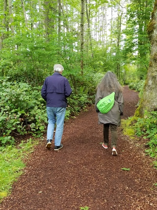 Couple walking down a forested path away from the camera.