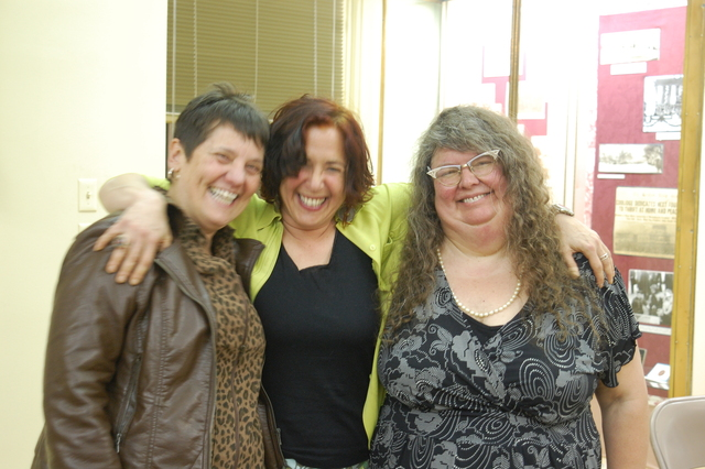 Three middle aged women are grinning in front of a lit library museum case. Hilary, in the middle in a lime jacket and black top, has her arms flung over the shoulders of the other two.