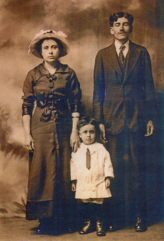 Mother, father and 3 year old child in a formal early 20th Century portrait.