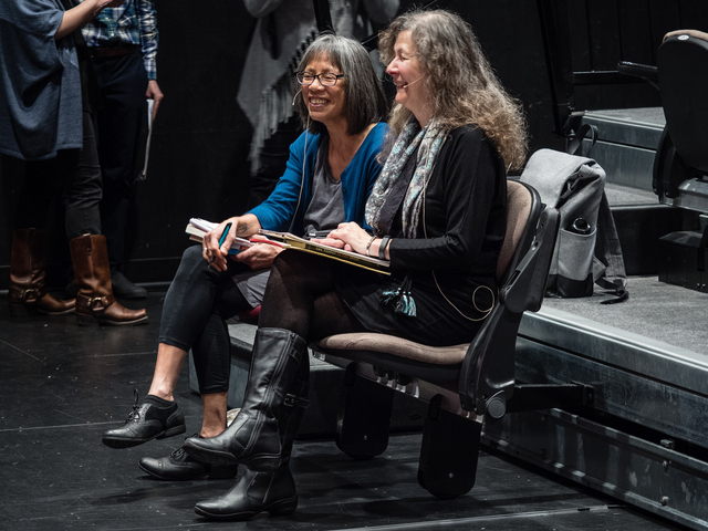Two women seated side by side in an auditorium, laughing nervously.
