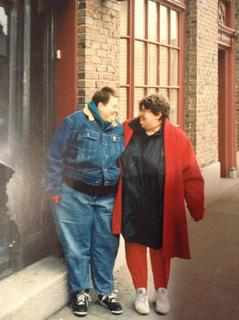Two fat white women look at each other, smiling, on a sidewalk.  Both have short brown hair. One is in jeans and a jean jacket. One (me) has on red pants, a black shirt and a red coat.