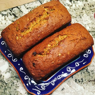 Two small bright orange loaves set on a contrasting platter.