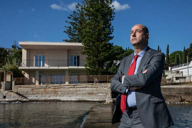 The entrepreneur Gianluca Calì, photographed in the small private harbour of his villa – previously owned by the former mafia boss Michele Greco, and now turned into a holiday house. Photograph: Alessio Mamo/The Guardian
