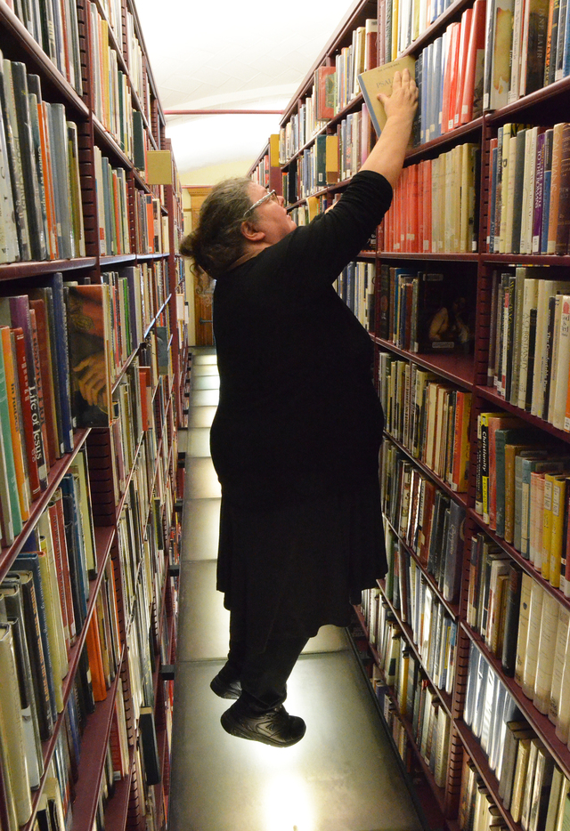 A fat, middle-aged white woman wearing black with brown hair in a bun stands on her toes on a lit glass floor between shelves of books, reaching for a book on a high shelf.